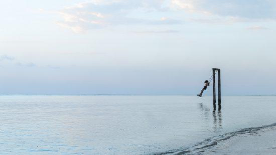girls swinging over water